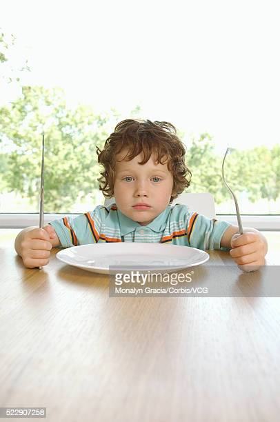 boy sitting at dinner table - impatient stock pictures, royalty-free photos & images