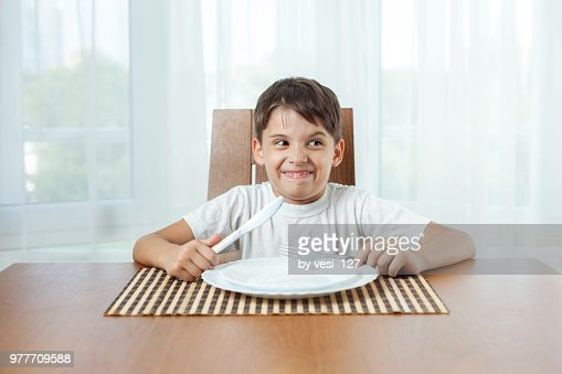 Boy Sitting At Dinner Table Waiting For Food Making Funny Faces Stock Photo Getty Images