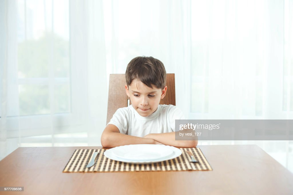 Boy Sitting At Dinner Table Waiting For Food Stock Photo