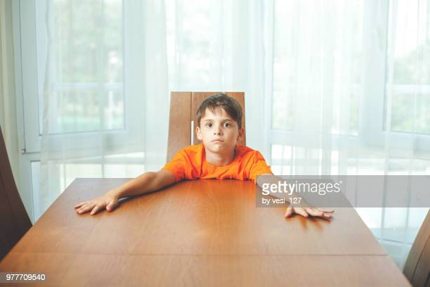 boy sitting at dinner table waiting for food - impatient stock pictures, royalty-free photos & images