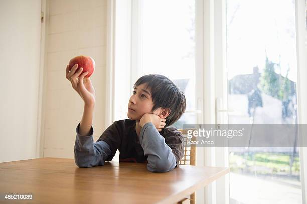 Boy sitting at table, holding an apple in front of him