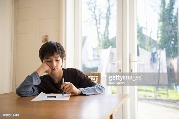 Boy sitting at table, holding pen to paper