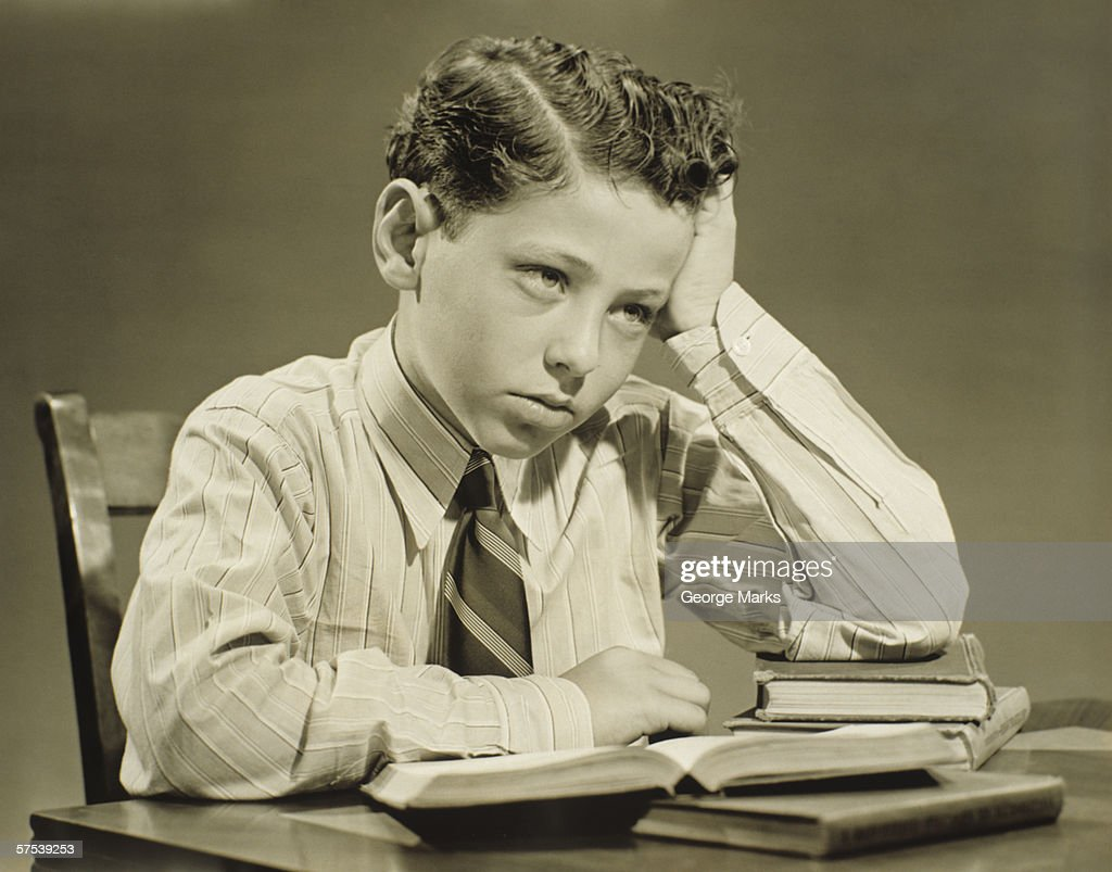 Boy (10-11) sitting at table over open book, head resting on hand, (B&W), close-up : Stock Photo