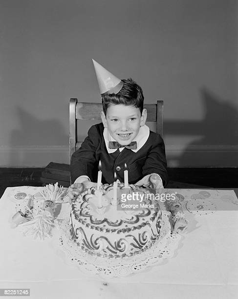 Boy (6-7) sitting at table with birthday cake, portrait