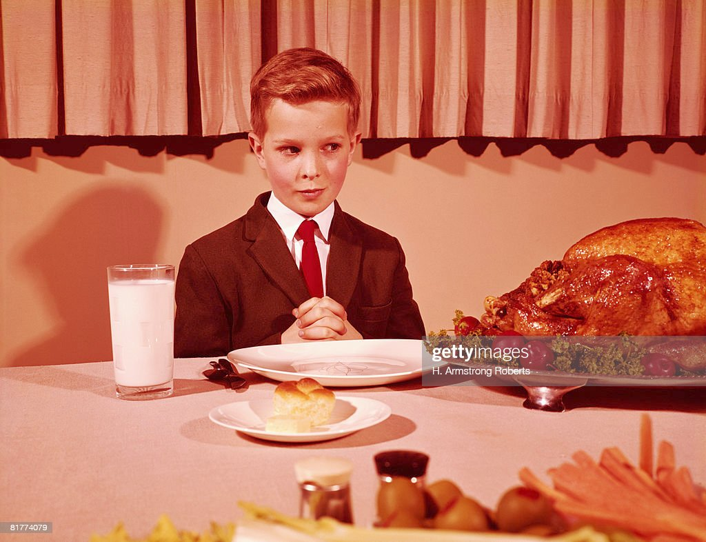 Boy sitting  at table with hands folded for grace prayer, looking at roast turkey. (Photo by H. Armstrong Roberts/Retrofile/Getty Images) : Stock Photo
