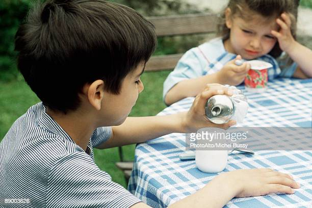 Boy sitting at table with sister,  pouring sugar yogurt