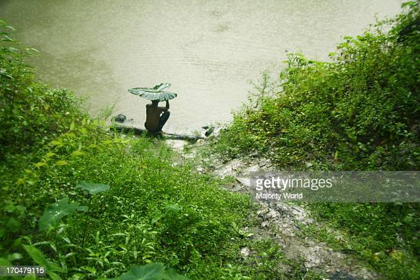 Boy sitting at the ghat of a pond in the rain at a village in Munshiganj, in Bangladesh. July 1, 2009.
