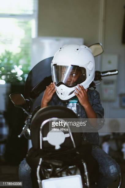 Boy sitting back to front on motorcycle wearing helmet