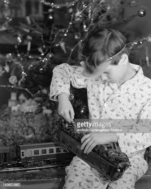 A boy sitting by a Christmas tree and adjusting the locomotive of a train set with a screwdriver circa 1955