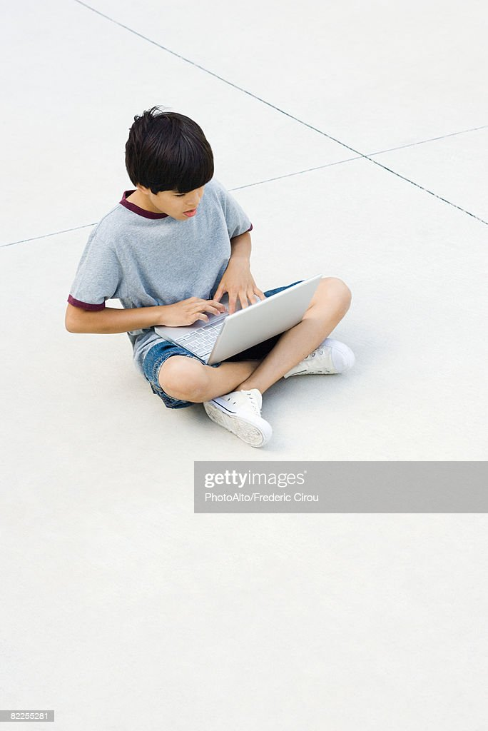 Boy sitting cross-legged on the ground, using laptop : Stock Photo