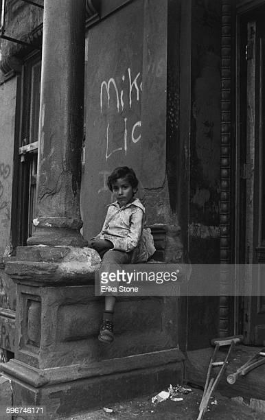 A boy sitting in a doorway in Harlem New York City circa 1975