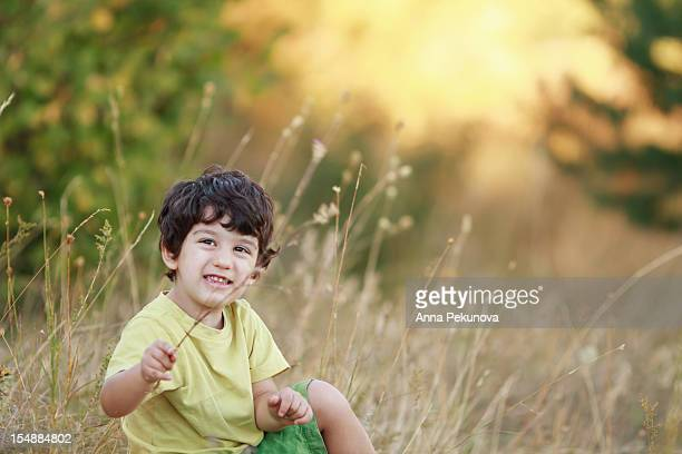 Boy sitting in a field of dry grass