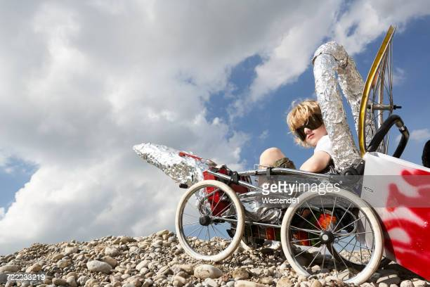 Boy sitting in a self-made rocket playing moon landing
