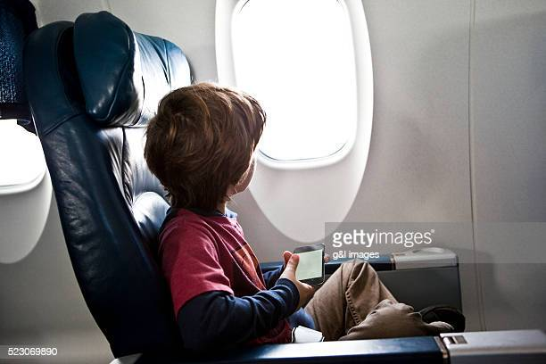 Boy (6-7 years) sitting in airplane