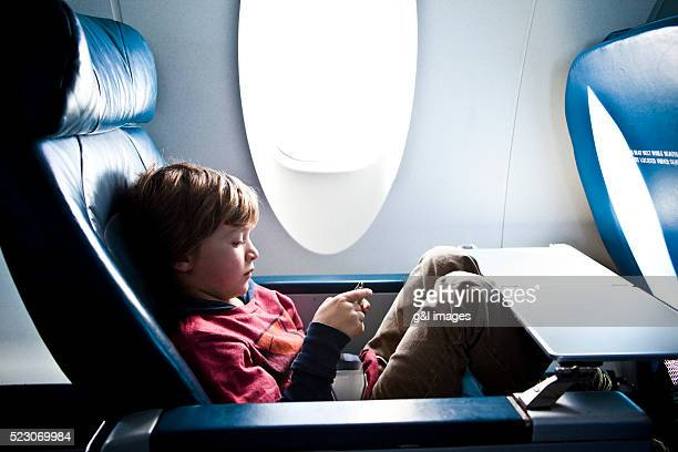 Boy (6-7) sitting in airplane