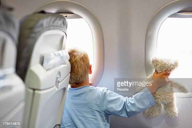 Boy sitting in an airplane holding a teddy