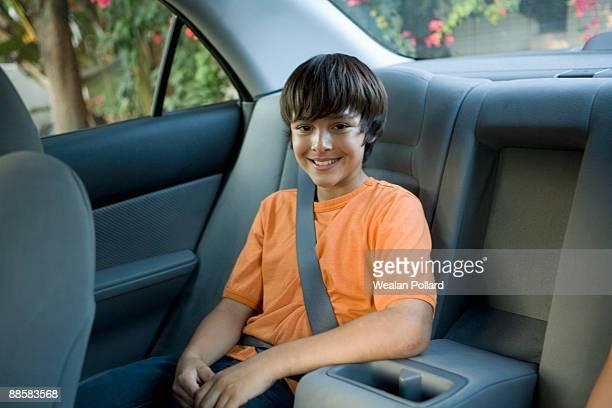 Boy sitting in back seat of car