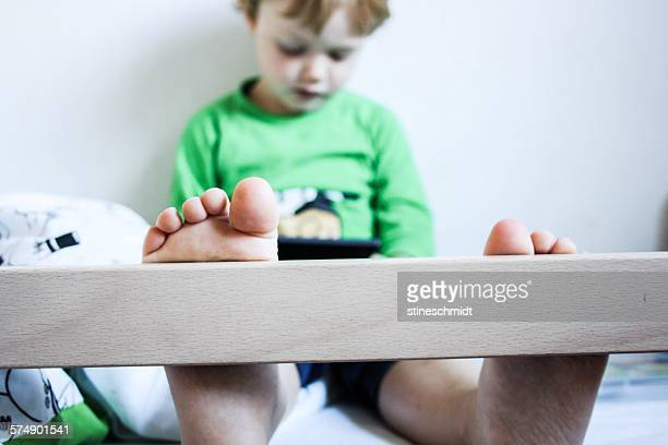 Boy sitting in bunk bed playing with digital tablet
