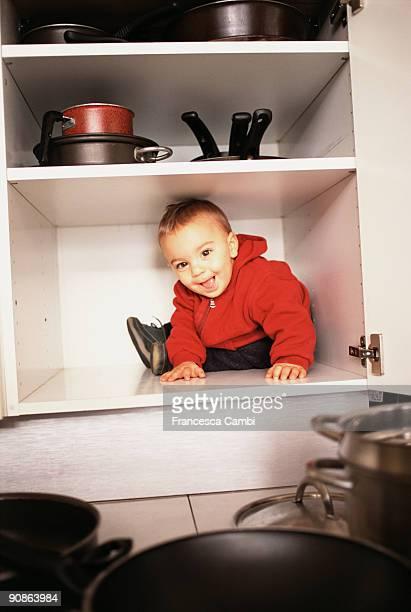 Boy sitting in cabinet