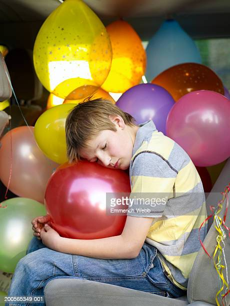 Boy (12-14) sitting in car with party balloons, eyes closed
