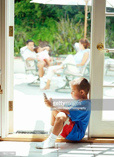 boy sitting in doorway playing - handheld video game stock pictures, royalty-free photos & images