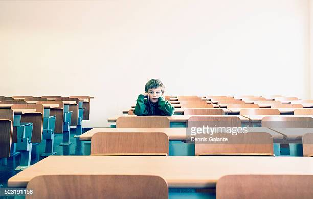 Boy Sitting in Empty Classroom