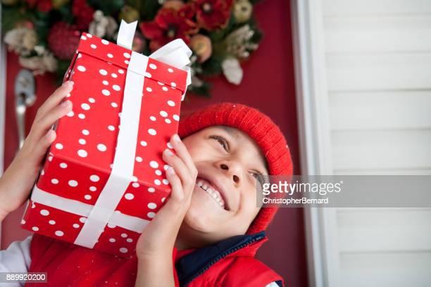 Boy sitting in front Christmas door step