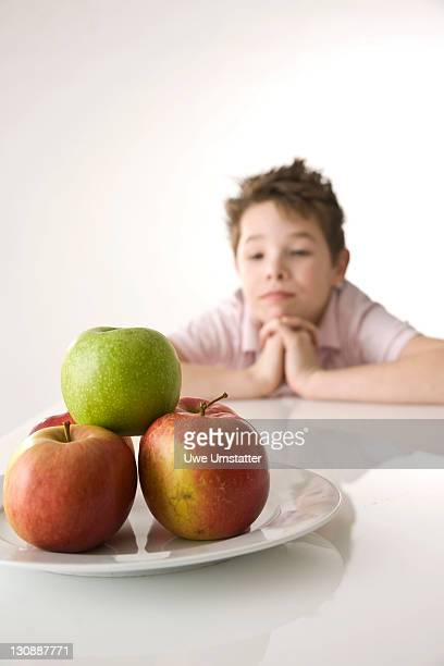 Boy sitting in front of a plate of apples, looking skeptical