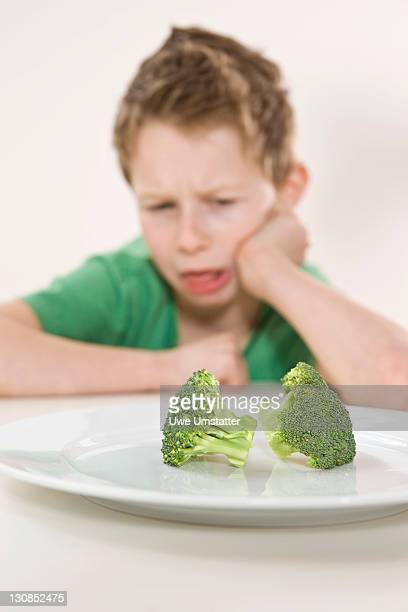 Boy sitting in front of a plate of broccoli with a disgusted look on his face