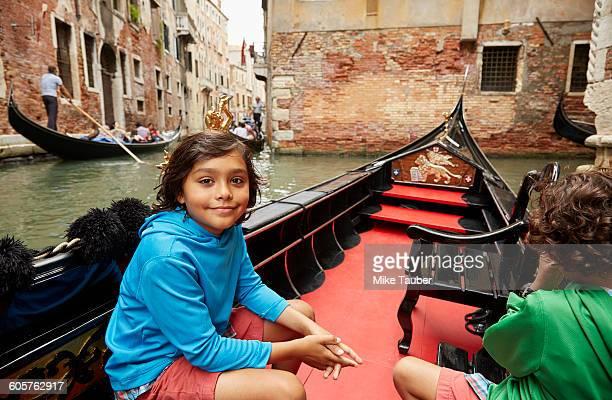 Boy sitting in gondola on Venice canal, Veneto, Italy