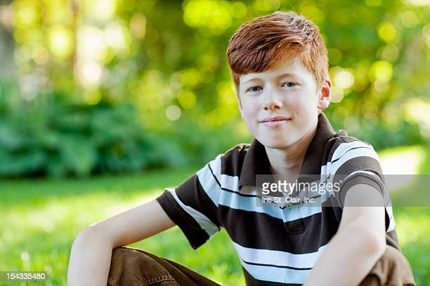 Boy (12-13) sitting in grass