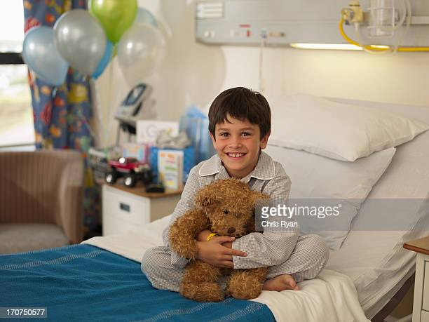 Boy sitting in hospital bed with teddy bear
