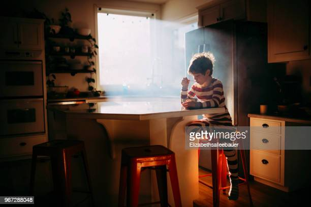 boy sitting in kitchen eating his breakfast in morning light - breakfast cereal stock pictures, royalty-free photos & images
