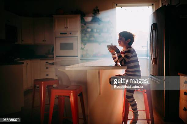 boy sitting in kitchen eating his breakfast in morning light - ready to eat stock pictures, royalty-free photos & images