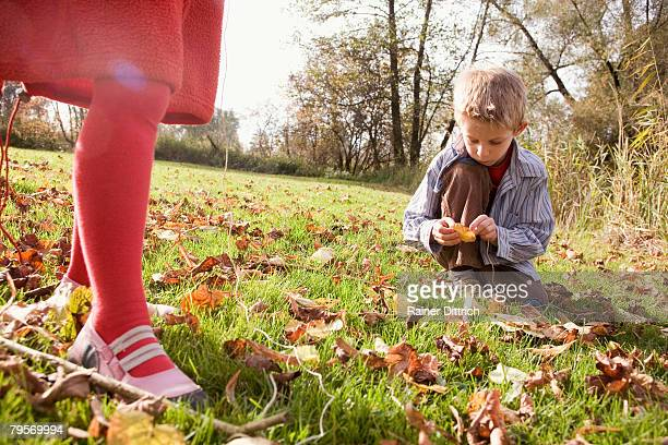 Boy (10-12) sitting in meadow legs of girl in foreground