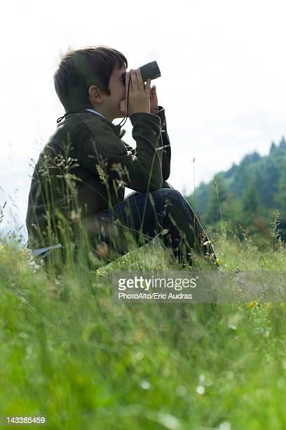 Boy sitting in meadow looking through binoculars