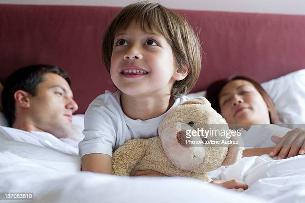 Boy sitting in parents' bed, hugging teddy bear
