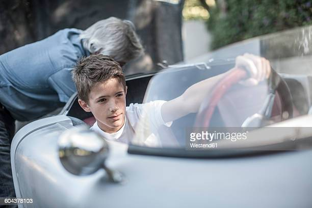Boy sitting in sports car with grandfather in background