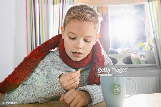 Boy sitting in the kitchen looking at tablet