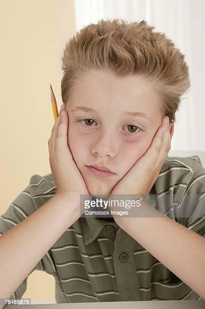 Boy sitting , looking miserable