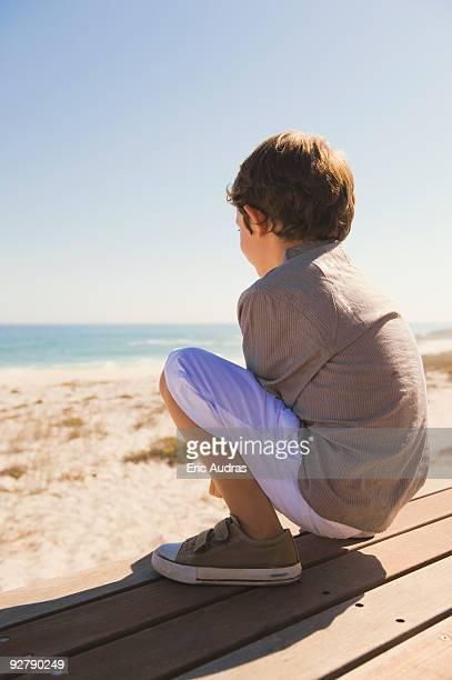 Boy sitting on a boardwalk