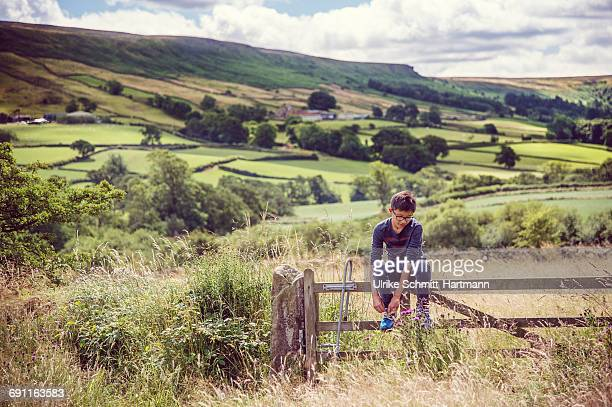 boy sitting on a fence in a national park - north yorkshire stock pictures, royalty-free photos & images