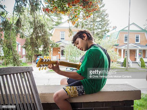 A boy sitting on a porch playing guitar