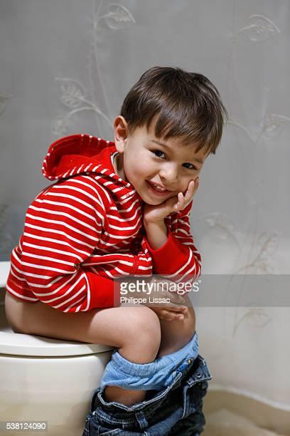 Boy sitting on a toilet