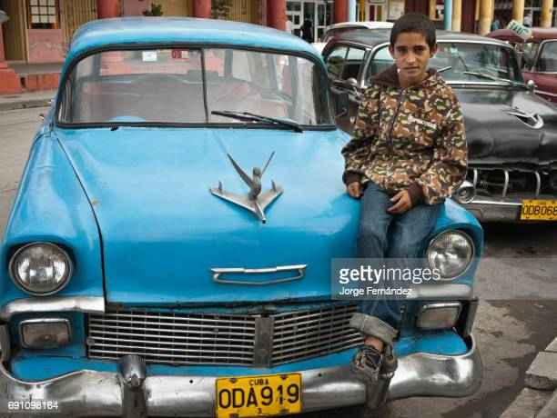 Boy sitting on a vintage taxi on the streets of Holguin