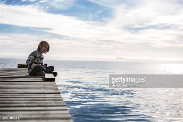 boy sitting on a wooden pier by the sea, aarhus, denmark - jutland stock photos and pictures