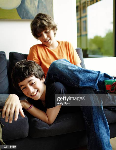 boy sitting on another boy on couch