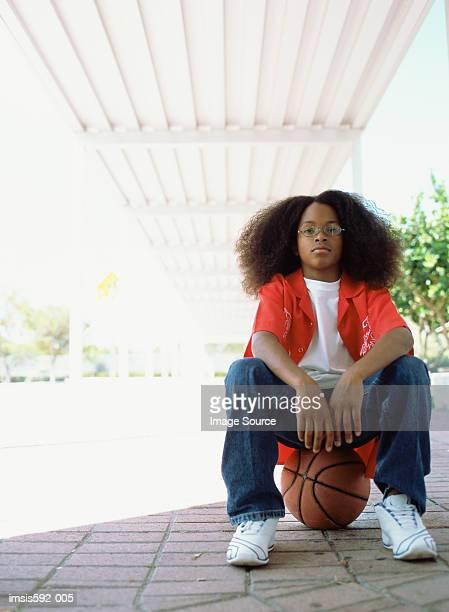 Junge sitzt auf basketball