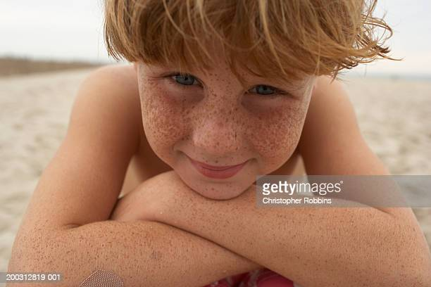 Boy (6-8) sitting on beach, leaning on knees, smiling, portrait