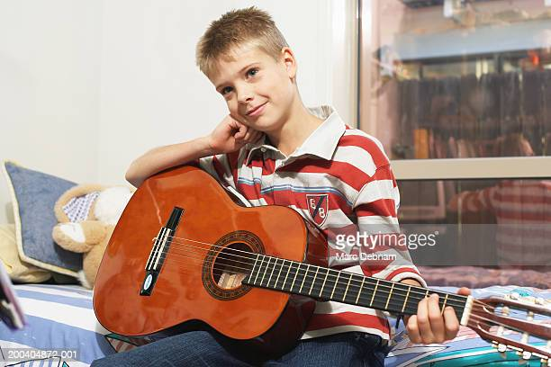 Boy (10-12) sitting on bed holding guitar, resting head on fist, smiling